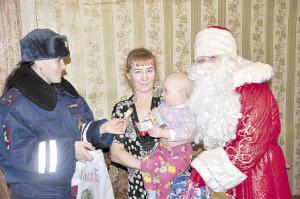 Наталья Кожевникова и Дед Мороз (Татьяна Оборина) с наилучшими пожеланиями вручили подарок маленькой девочке Вике.