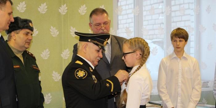 Алексей Медведев прикрепляет значок юнармейца ученице Миньковской школы Анастасии Марковой.