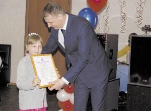 Владимир Порошин вручает Приветственное письмо ученице Подболотной школы Александре Крюковой.