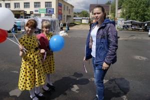 Участницы фольклорного коллектива «Горница» (слева) раздают трехцветные ленточки во время акции «Российский триколор».
