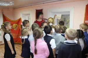Специалист экспозиционной и выставочной деятельности Дженни Синицына знакомит ребят с материалами выставки.